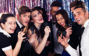 Portrait of happy multiethnic friends singing into microphones at karaoke party