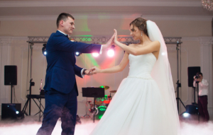 Beautiful newlywed couple first dance at reception, smoke surrondings