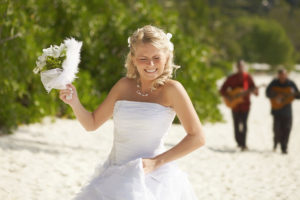 Gorgerous bride walking to wedding ceremony on the beach with bouquet. Beautiful hawaii wedding. Tropical carribean wedding moments.